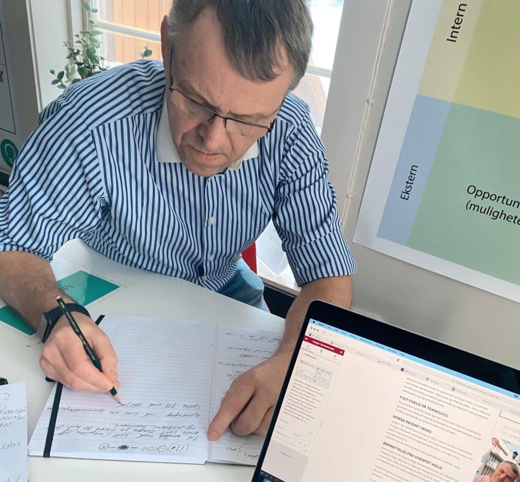 Mann med briller og stripete skjorte bak en laptop